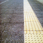 Πεζοδρόμιο με βοτσαλόπλακες και πλάκες ΑΜΕΑ